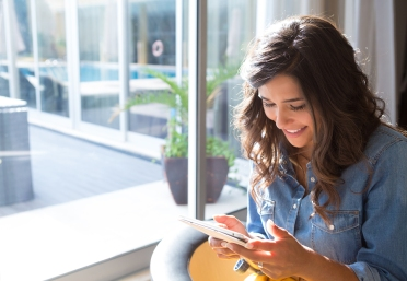 Fashion woman using tablet with sunbeams and lens flare